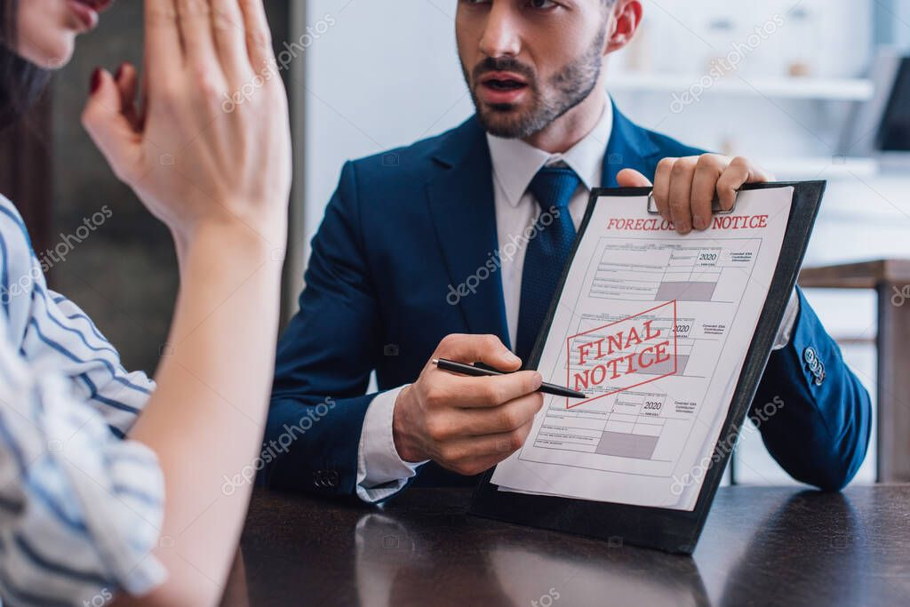 Cropped view of woman and collector pointing with pen at documents with foreclosure and final notice lettering at table stock vector