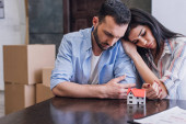 Photo Woman leaning to upset husband at table with house model and documents in room