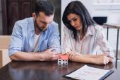 Rozrušit bankroty při pohledu na model domu v blízkosti dokumentů u stolu na pokoji