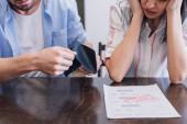 Oříznutý pohled na muže držícího kabelku poblíž ženy u stolu s dokumentem s posledním oznámením nápis na pokoji