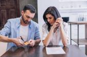 Muž řezání kreditní karty poblíž žena se zaťatými rukama u stolu s dokumentem v pokoji