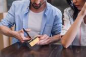 Vágott kilátás férfi vágás hitelkártya közelében nő az asztalnál
