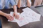 Oříznutý pohled na muže a ženu s dokumenty s zabavením a poslední oznámení nápisy u stolu
