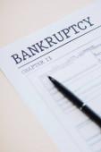 Vysokoúhlé zobrazení pera na dokumentu s bankrotem a 13. kapitolou na bílém pozadí
