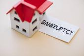 Vysoký úhel pohledu na kartu s bankrotem a modelem domu na bílém