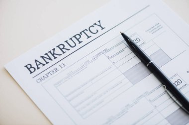 High angle view of pen on document with bankruptcy and chapter 13 lettering on white stock vector