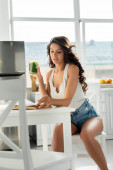 Selective focus of beautiful woman reading book while drinking smoothie at table in kitchen