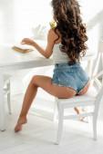 Vissza kilátás szexi nő farmernadrág olvasókönyv az asztalnál
