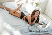Vysoký úhel pohledu na sexy žena s notebookem s úsměvem a ležící na posteli v ložnici