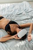 Magas szög kilátás szexi nő virtuális valóság headset mosolygós és fekvő ágyban a hálószobában