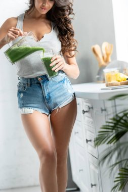 Cropped view of young woman pouring smoothie from blender in glass in kitchen stock vector