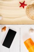 Top kilátás okostelefon közelében napvédő fehér fa deszkák és kagylók homokon