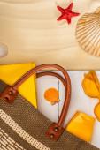 Blick auf Tasche, Sonnencreme und Buch auf weißen Holzplanken in der Nähe von Muscheln auf Sand