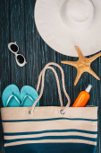 Top view of starfish, flip flops near sun hat and sunglasses on dark wooden surface