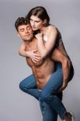 hemdloser Mann huckepack attraktive Freundin isoliert auf grau