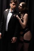 sexy Frau in Unterwäsche und Strümpfen ziehen Krawatte schöner Mann im Anzug auf schwarz