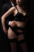 oříznutý pohled na muže v obleku dotýká sexy žena ve spodním prádle a punčochy izolované na černé