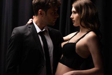 Profile of handsome man in suit hugging seductive girl in underwear on black stock vector