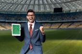 vidám fiatal üzletember öltöny és szemüveg tartja digitális tabletta focimeccs a képernyőn, és azt mutatja, igen gesztus a stadionban