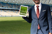 cropped view of smiling young businessman in suit holding digital tablet with healthcare app at stadium