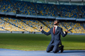 young businessman in suit standing on knees with smartphone and trophy at stadium, sports betting concept