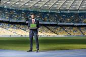 mosolygós fiatal üzletember öltönyben mutatja laptop futball alakzat a képernyőn a stadionban