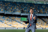 boldog fiatal üzletember öltönyben tartja laptop futballpálya és formáció a képernyőn, és azt mutatja, igen gesztus a stadionban