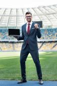 mosolygó fiatal üzletember öltönyben mutatja igen gesztus, miközben tartja laptop üres képernyőn a stadionban