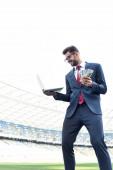 nízký úhel pohledu na šťastný mladý podnikatel v obleku držení notebooku a peněz na stadionu, sportovní sázení koncept