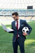 mosolygós fiatal üzletember öltönyben laptop és focilabda a stadionban, sportfogadás koncepció