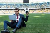 Fényképek boldog fiatal üzletember öltönyben laptop és focilabda ül a focipályán a stadionban, sportfogadás koncepció