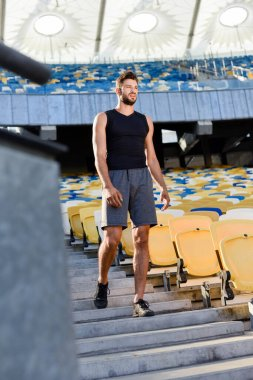 selective focus of young sportsman walking on stairs at stadium