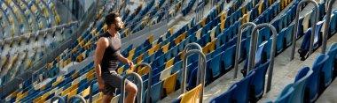 Young sportsman walking on stairs among seats at stadium, panoramic shot stock vector