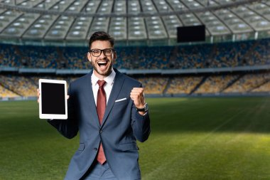 Cheerful young businessman in suit and glasses holding digital tablet with blank screen and showing yes gesture at stadium stock vector
