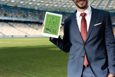 cropped view of smiling young businessman in suit holding digital tablet with formation on screen at stadium