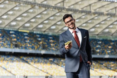 Smiling young businessman in suit and glasses giving money at stadium stock vector