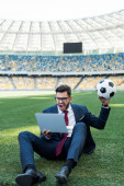 fiatal üzletember öltönyben laptop és focilabda ül a focipályán a stadionban és kiabál, sportfogadás koncepció