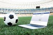 KYIV, UKRAINE - Június 20, 2019: foci labda és laptop a facebook honlapján füves focipálya stadionban