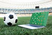 futball labda és laptop alakzat a képernyőn füves focipályán a stadionban