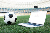 KYIV, UKRAINE - JUNE 20, 2019: soccer ball and laptop with google website on grassy football pitch at stadium