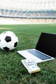 fotbalový míč, peníze a notebook s prázdnou obrazovkou na travnatém fotbalovém hřišti na stadionu, koncept online sázení