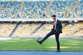 fiatal üzletember öltönyben és szemüvegben focilabdázik a stadionban