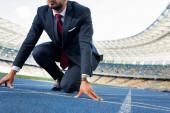 oříznutý pohled na mladého podnikatele v obleku v počáteční poloze na běžecké dráze na stadionu
