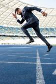 oldalnézetben fiatal üzletember öltönyben fut a stadionban