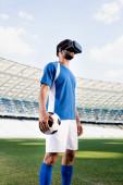 Fotografie Fußballprofi in blau-weißer Uniform mit Ball auf dem Fußballplatz im Stadion