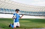 Fußballprofi in blau-weißer Uniform mit Ball auf Knien und JA-Geste auf dem Fußballplatz im Stadion