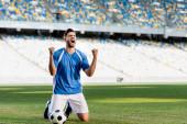 Fényképek érzelmi profi focista kék-fehér egyenruhában, golyóval a térdén áll a focipályán, és igen gesztust mutat a stadionban