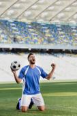 érzelmi profi focista kék-fehér egyenruhában, golyóval a térdén áll a focipályán, és igen gesztust mutat a stadionban
