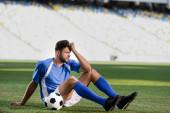 smutný profesionální fotbalista v modré a bílé uniformě sedí s míčem na fotbalovém hřišti na stadionu