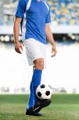 Ausgeschnittene Ansicht eines Fußballprofis in blau-weißer Uniform mit Ball auf dem Fußballplatz im Stadion